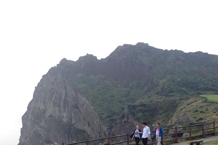 城山日出峰をバックに記念撮影